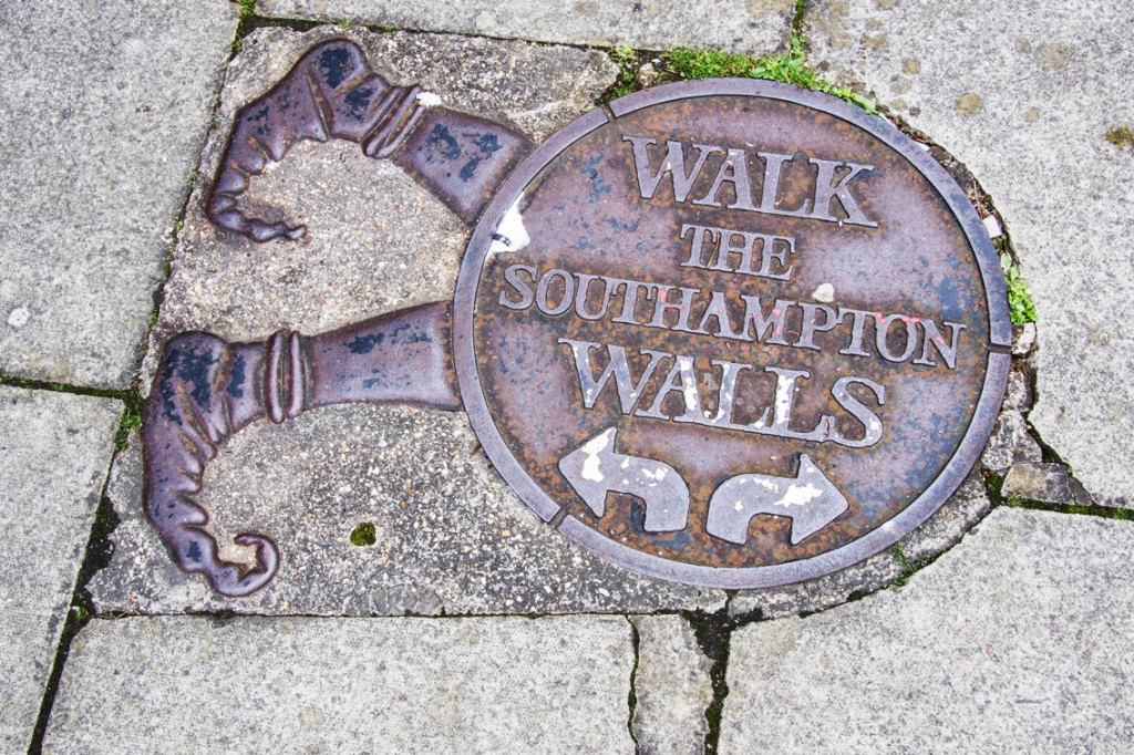 """walk the southampton walls"", written on an odd sign, a circle with feet, on the road."